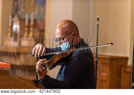 Terni,italy May 20 2021:violinist In Church With Medical Mask Playing Violin