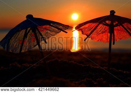 Paper Cocktail Umbrellas In Sand On Seashore At Sunset Dawn Close-up.
