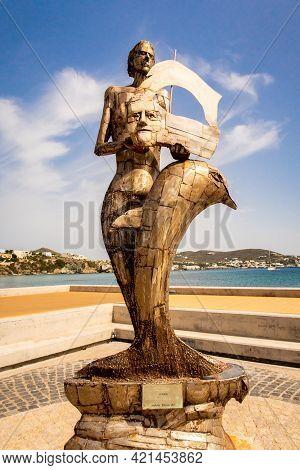 Finikas, Siros Island, Greece, 27.05.2019. Bronze Sculpture With A Human And Dolphin In Finikas Mari