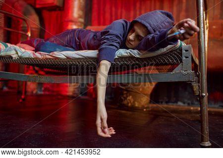 Drug addict woman sleeps on bed in den