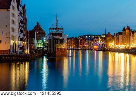 Gdansk Night City Riverside View With Moored Ship. View On Famous Facades Of Old Medieval Houses On