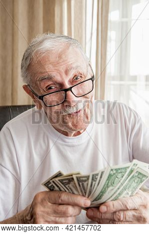Silver-haired 88-year-old Man With Glasses Happily Counts His Savings. Solvency In Retirement. The O