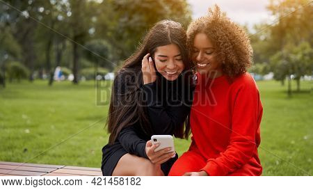Diversity And Feminity Concept. Happy Smiling Confident Young Mixed Race Women Sitting Bench Park Ou