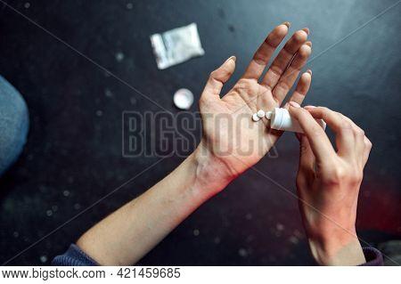Drug addict woman holds pills, junkie concept