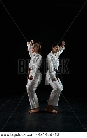 Female karatekas in kimono, combat stance