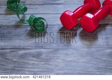 Sport Theme Fitness Healthy Lifestyle Dumbbells On Wooden Floor. Small Dumbbells, Dumbbells And Gree