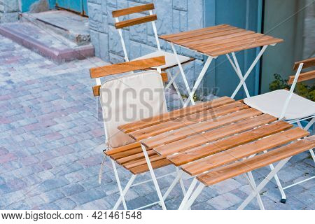 Light Wooden Table And Chairs With Textile Lining Stands On The Sidewalk Near A Restaurant. Cozy Spo