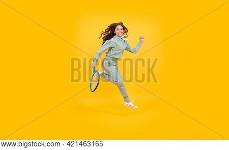 Energetic Child With Tennis Racquet. Teen Girl Run To Training. Dedicated To Fitness