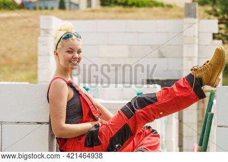 Woman In Dungarees Relaxing After Hard Work On Construction Site. Young Female Lying Outdoor Taking