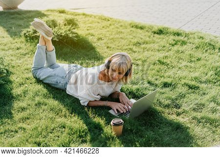 Mature Adult Woman In Headphones Using Laptop, Lying On The Grass Outdoors In Summer Park. Happy And