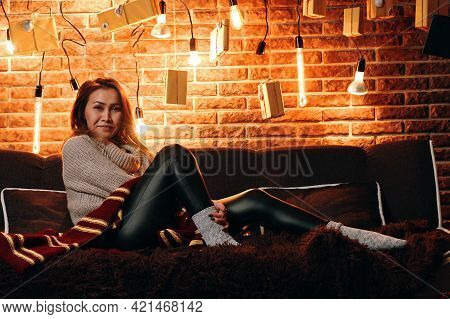 Cute Girl Sitting On Couch. Christmas And New Year Atmosphere. Different Shapes Light Bulbs On Backg