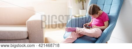 Cute Girl Sitting On The Sofa And Playing In The Smartphone.