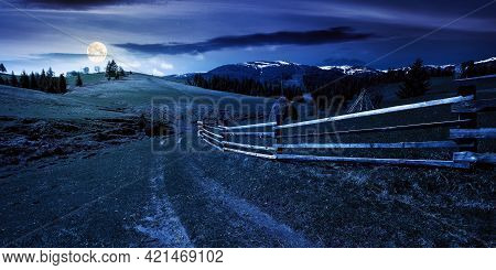 Mountainous Rural Landscape At Night In Spring. Path Through Grassy Field. Wooden Fence On Rolling H