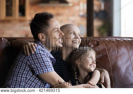 Happy Hairless Young Woman With Cancer Relaxing On Couch