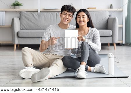 Happy Sporty Asian Couple Showing Digital Tablet With Blank Screen