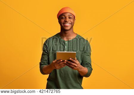 Happy Black Millennial Guy Holding Digital Tablet And Smiling At Camera