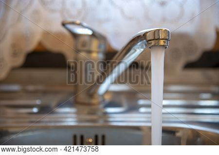 Sink With A Tap In A Kitchen. Kitchen Faucet With Running Water.