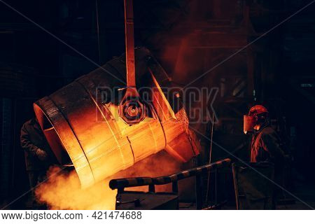 Ladle Container With Liquid Molten Metal And Worker In Protective Helmet And Face Mask, Industrial M
