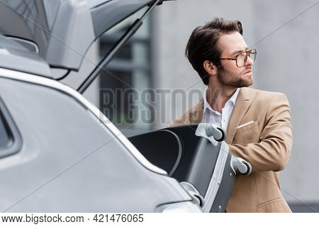 Distracted Man In Glasses And Suit Putting Baggage In Blurred Car Trunk.