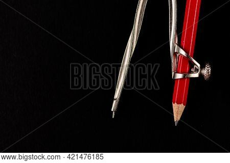 A Metal Compass With Red Pencil Attached With It Shot Over Black Background And Copy Space On The Le