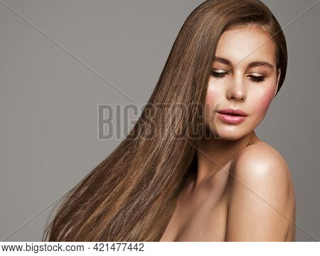 Brunette Woman With Straight Long Shiny Hair. Beauty Model Glowing Skin Face Make Up Portrait. Beaut