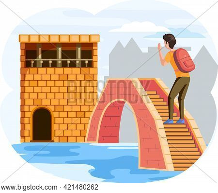 Male Traveler Stands On Small Stone Bridge Over River In Old Town With Low Brick Ancient House, Famo
