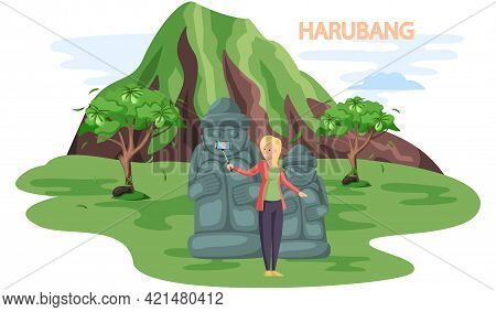 Tourist Takes Photo Near Stone Sculptures And Tropical Plants In Stone Park. Statue Of Dol Hareubang