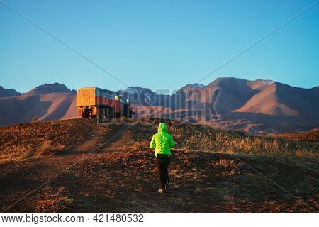Orange Truck And Girl Tourist In Vivid Green Jacket On Hill With View To Great Brown Mountain With S