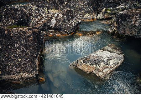 Scenic Nature Background Of Turquoise Clear Water Stream Among Rocks With Mosses And Lichens. Atmosp