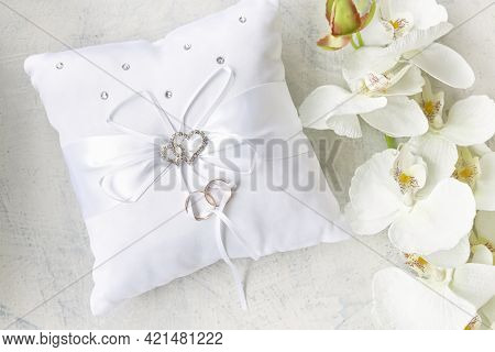 White Pillow For Wedding Rings With Rings And Rhinestone Hearts Near White Orchid On A White Texture