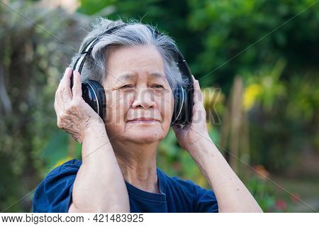 Senior Woman Wearing Wireless Headphone Listening To A Favorite Song While Standing In A Garden. Asi
