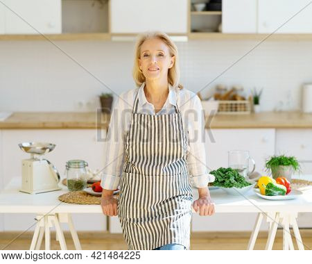 Portrait Of Beautiful Positive Mature Woman In Apron In Kitchen Looking At Camera And Smiling, Retir