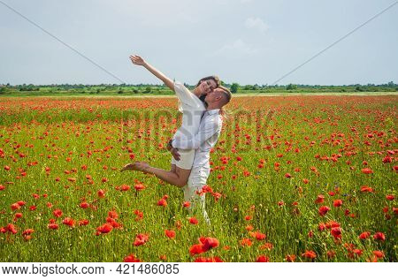 Romantic Relationship. Beautiful Couple In Love. Man And Woman In Poppy Flower Field. Summer Vacatio