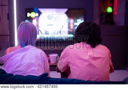 Beautiful Blue Haired Girl And Young Guy Holding Gaming Contorllers Playing Video Games At Home.