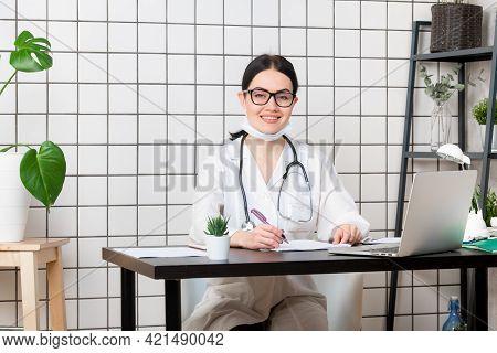 Doctor Wearing Medical Mask At Desk At Office Looking At Camera
