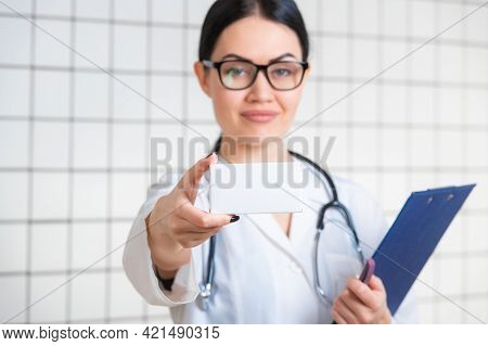 A Friendly Cute Girl With Dark Hair And Glasses, Wearing A Lab Coat, Reads Carefully The Information
