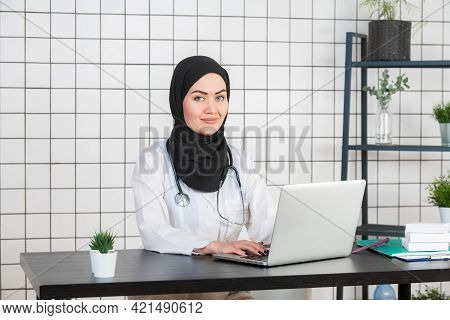 Young Smiling Woman Sitting At Desk, Working On Computer With Medical Documents In Light Office In H