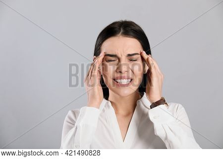Woman Suffering From Migraine On Grey Background