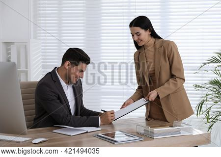 Secretary Bringing Document For Signature To Her Boss  In Office