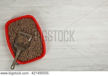Cat Litter Tray With Filler And Scoop On White Wooden Floor, Top View. Space For Text