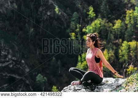 An Attractive And Healthy Young Woman Does Yoga In The Mountains At Dawn. Yoga In The Fresh Air. Hap