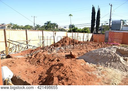 Construction Site With Construction Sand, Wooden Sidings, Excavation For Foundation In The City Back