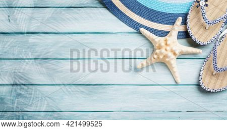 Beach accessories. Flip flops, hat and starfish on wooden background. Top view flat lay with copy space