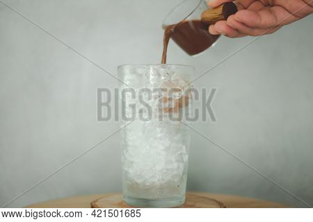 Pour Mocha Coffee Over Ice Cubes In Glass To Make Iced Coffee At Coffee Shop.