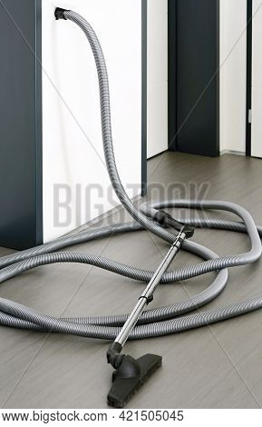 Long Central Vacuum Cleaner Hose Laid On The Grey Floor In The Room. Hose Of Central Vacuum Cleaner
