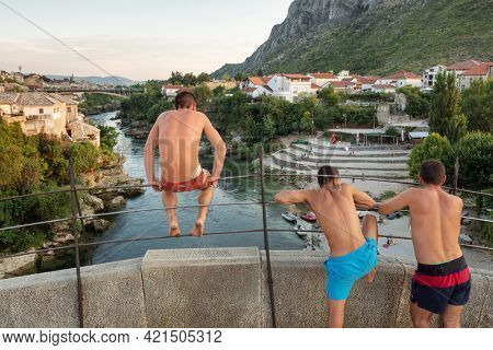Mostar, Bosnia and Herzegovina - August 30, 2019: A jumper from the Old Bridge sit on the top of the main arch of the bridge in Mostar, Bosnia and Herzegovina.