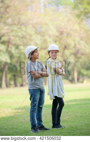 A Half-thai-indian Boy  And A Mixed-thai-european Girl Wearing A Helmet Holds A Blueprint And Expect