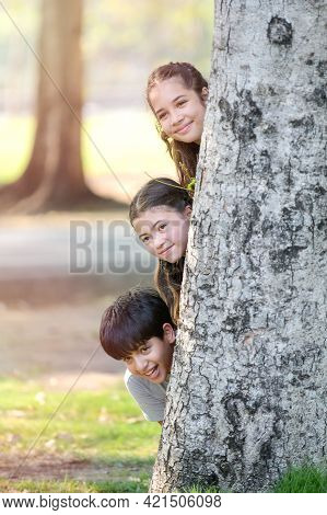 A Half-thai-indian Boy And A Mixed-thai-european Girl Friend Play Secretly Behind A Big Tree In A Pa