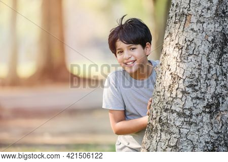 A Half-thai-indian Boy Play Secretly Behind A Big Tree In A Park While Learning Outside Of School