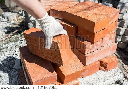 Construction work in a private house. A bricklayer takes bricks from a stack.